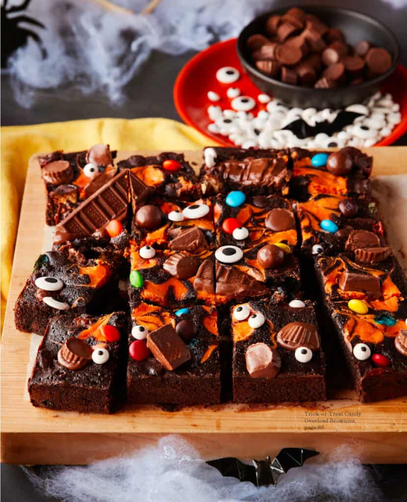 Brownies covered in Halloween candy and an orange swirl sliced on a cutting board.