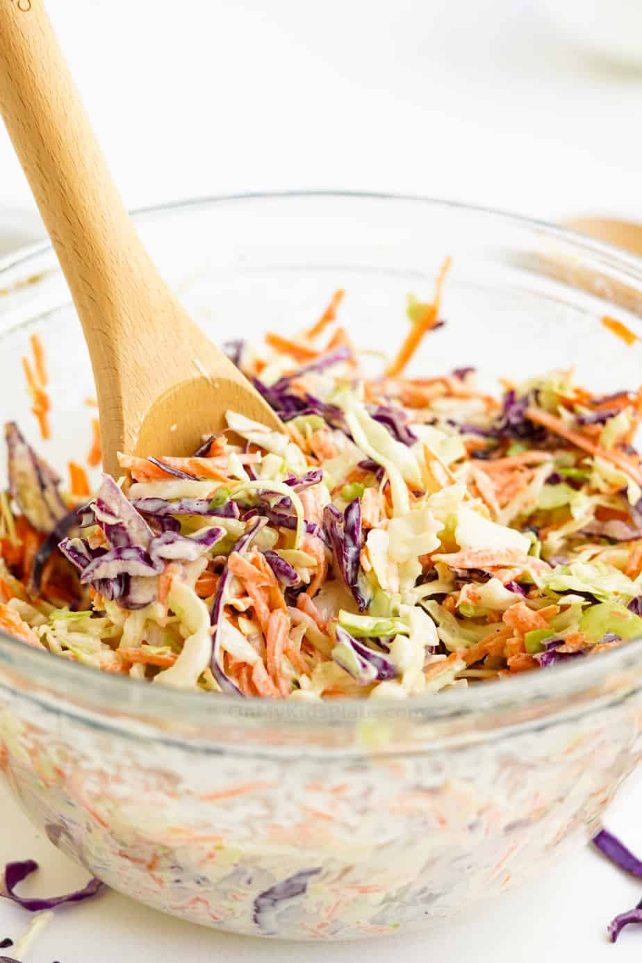 Mixing cabbage with dressing to make coleslaw in a large clear bowl from the side with a wooden spoon.