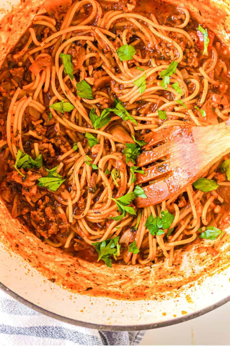 Close up of pasta in tomato sauce, ground turkey and parsley in a dutch oven with a wooden spoon.