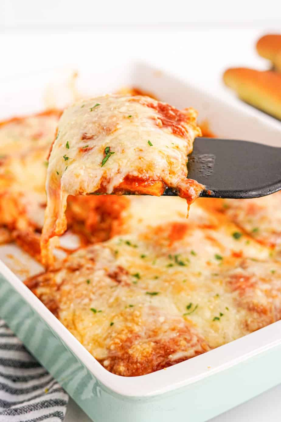 A serving of baked ravioli covered in cheese being pulled out of a casserole dish with a spatula