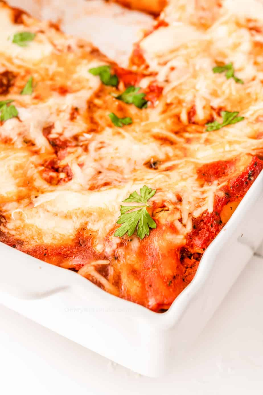 The angled corner of a pan of baked ziti covered in gooey cheese.
