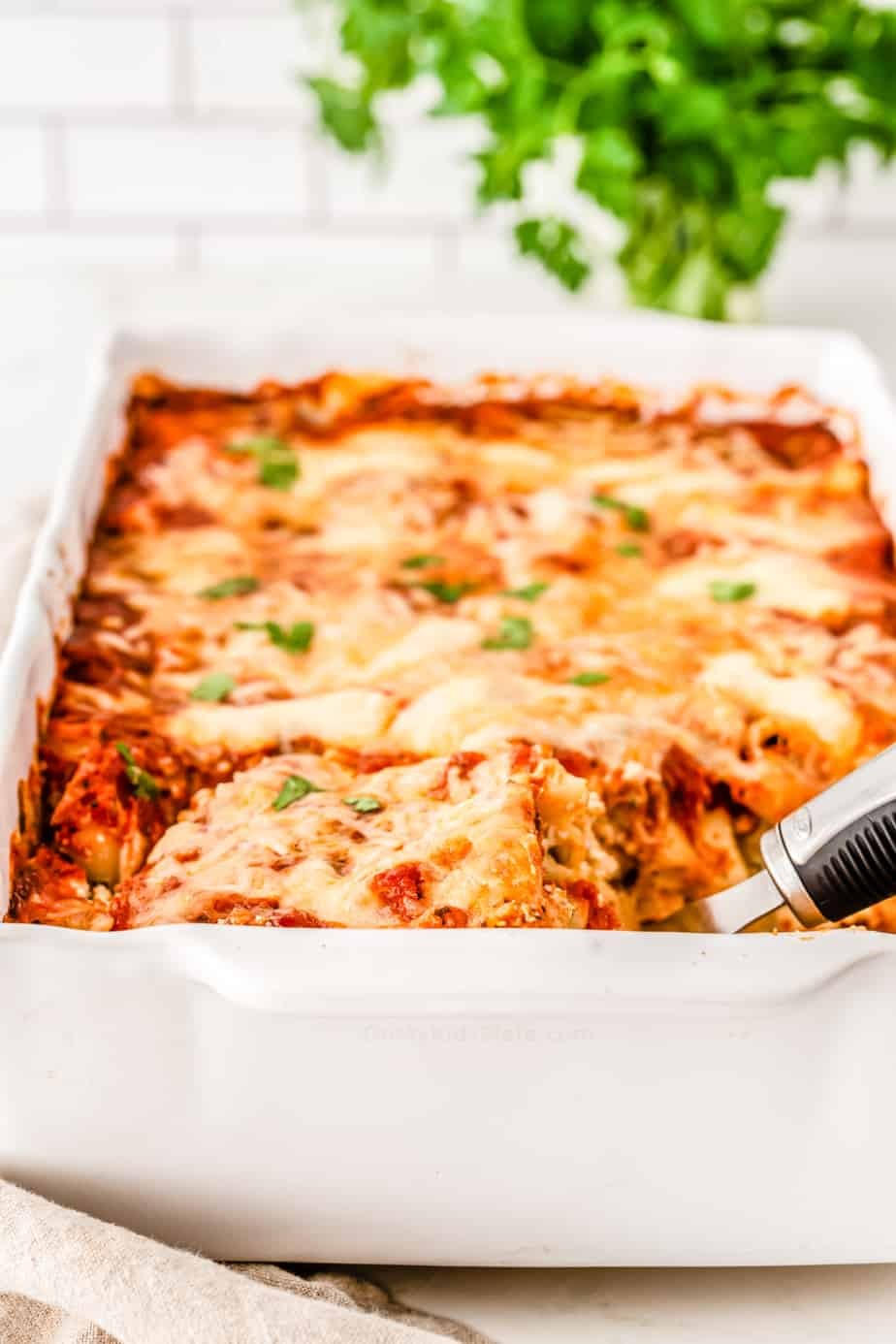 Baked ziti covered in a melted cheese in a pan with a spoon beginning to lift out a serving.