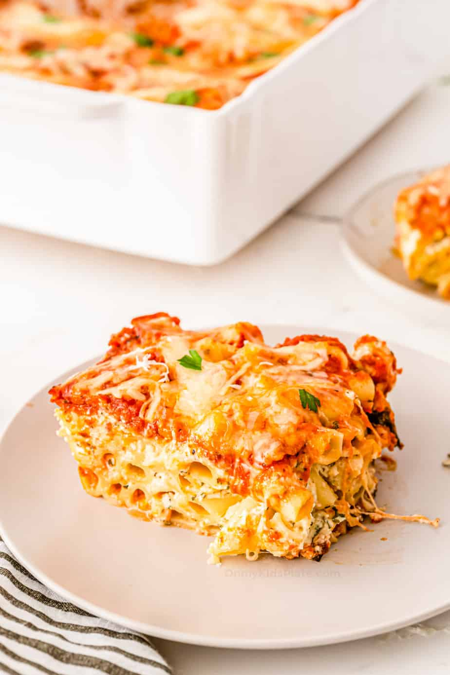 A plate full of cheesy baked ziti with a baking pan full of pasta in the background.