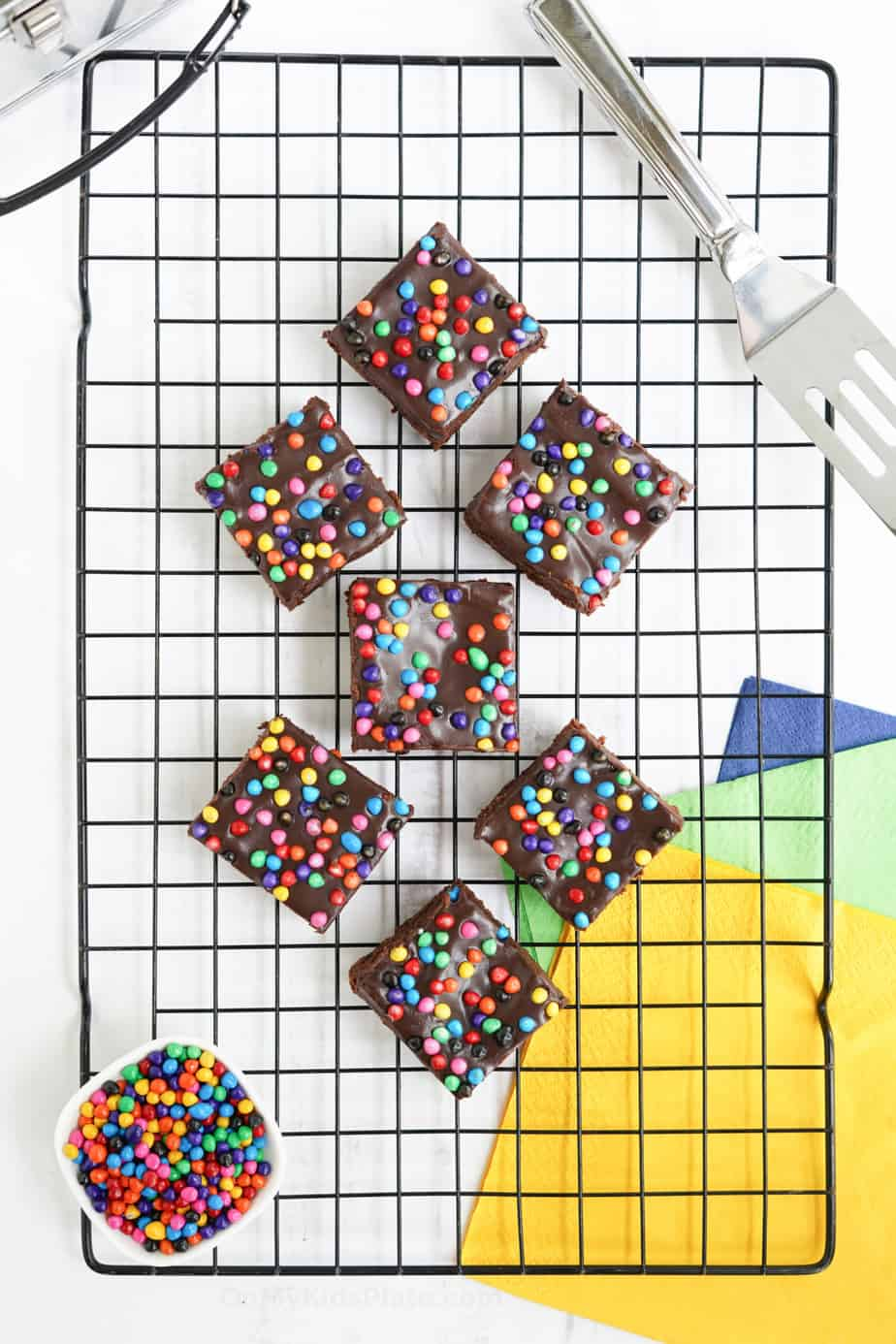 Brownies with rainbow sprinkles sliced on a cooling rack