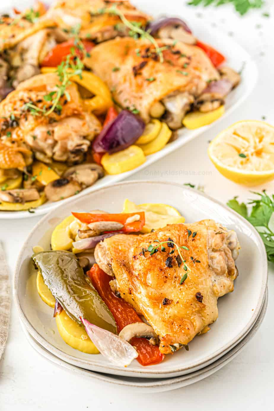 Baked Chicken Thighs on a plate  with peppers, onions, squash and mushrooms. A sheetpan full of chicken and vegetables in the background.