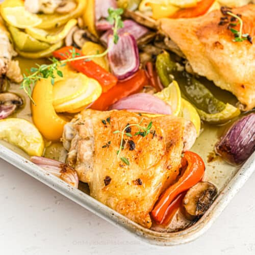 Baked chicken thighs and vegetables close up on the corner of the pan