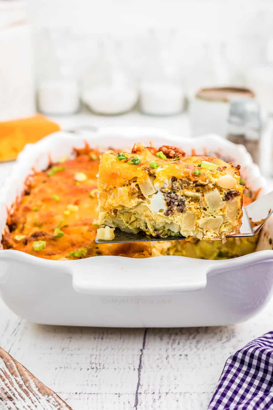Slice of breakfast casserole being lifted from the pan with a spatula showing the egg, sausage and potato in the sllice.