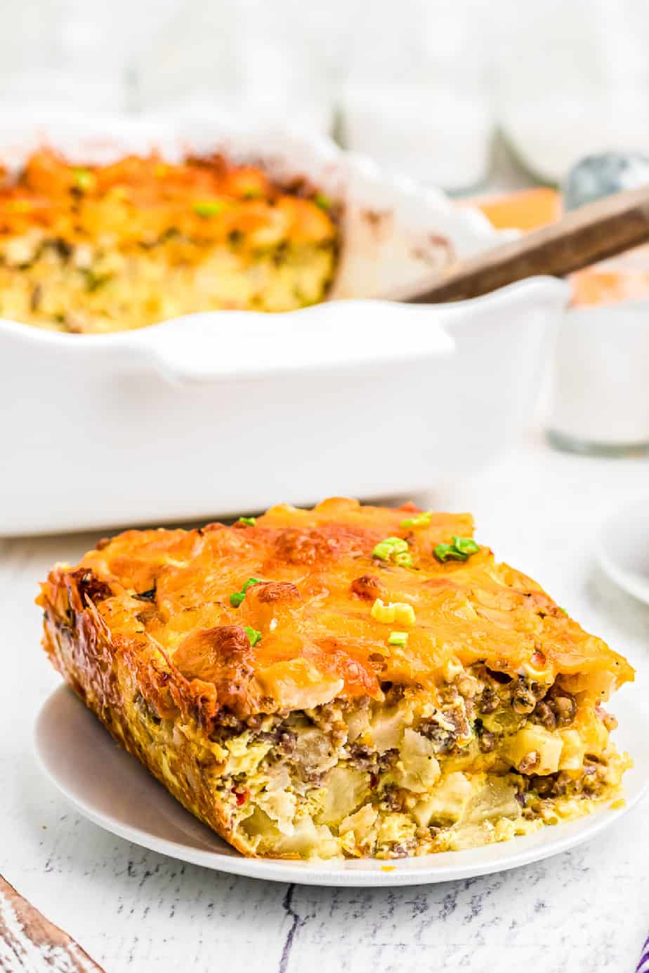Slice of egg sausage potato breakfast bake  on a plate from the side with a casserole dish in the background.