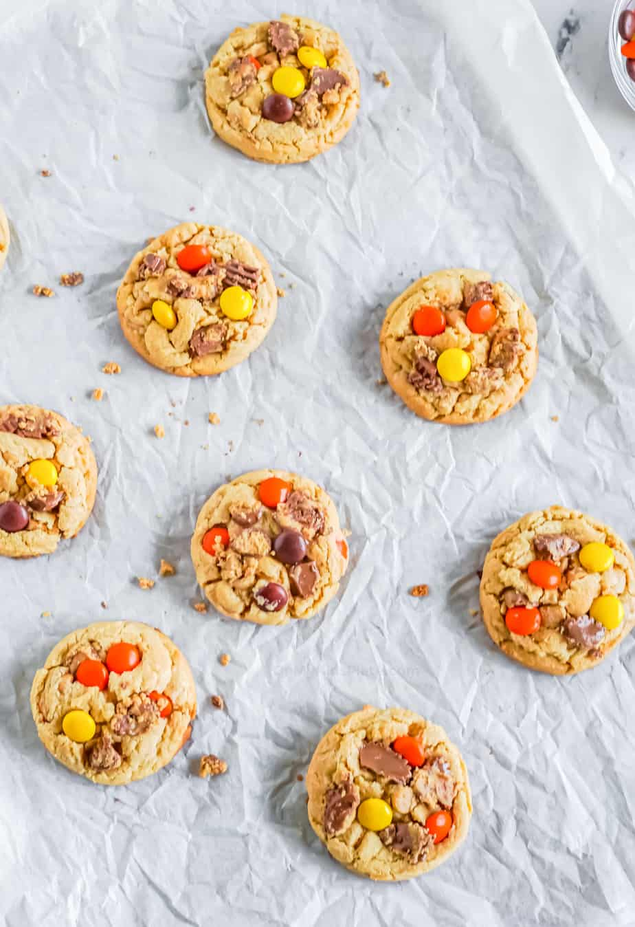 Cookies baked on the pan with peanut butter cups and Reese's pieces pressed into the top of the cookies.