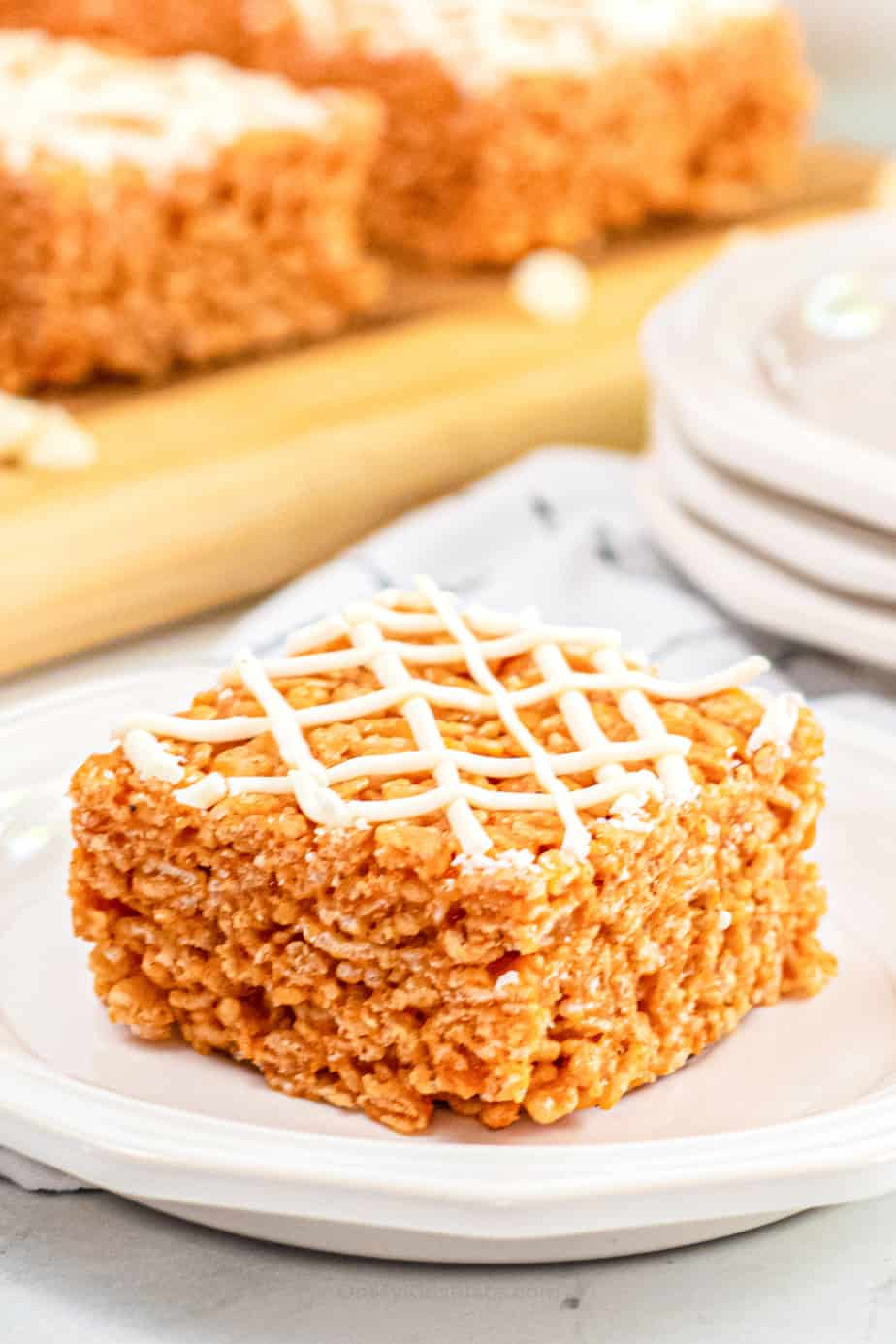 Pumpkin rice krispie treat drizzled with white chocolate on a plate up close