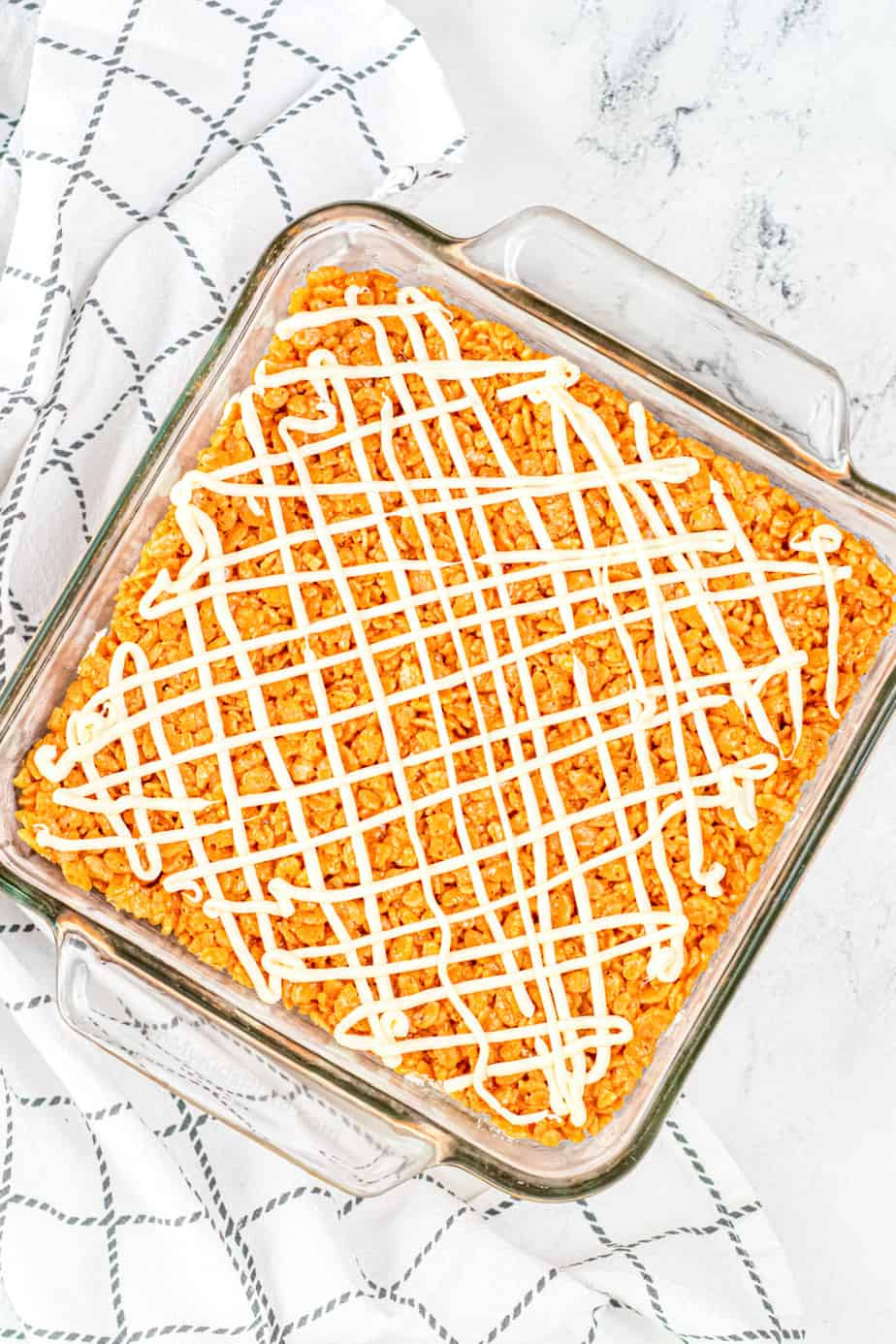 A square glass pan of pumpkin rice krispie treats drizzled with white chocolate.