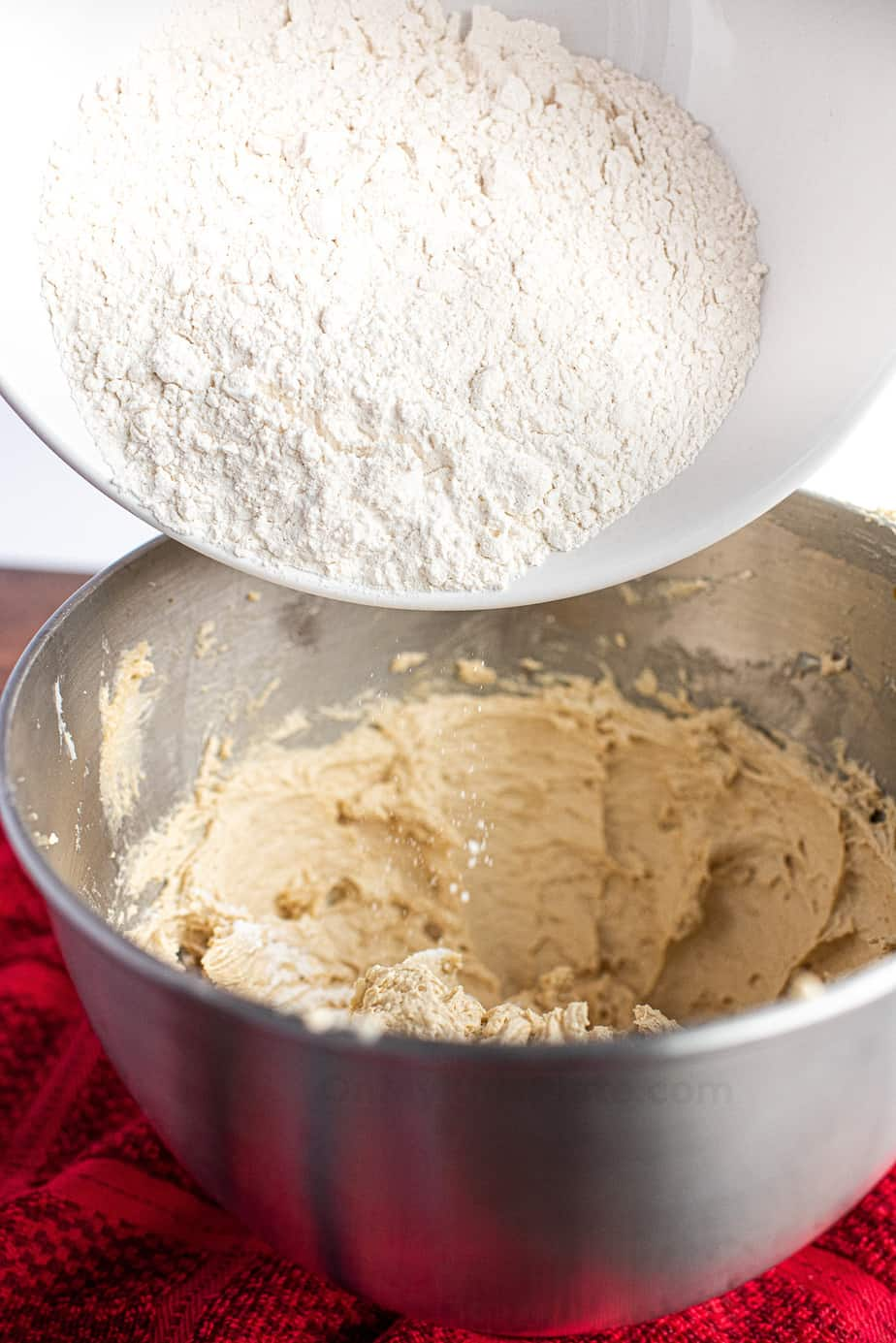 Pouring dry ingredients from a bowl to wet cookie ingredients below to mix into cookie dough.