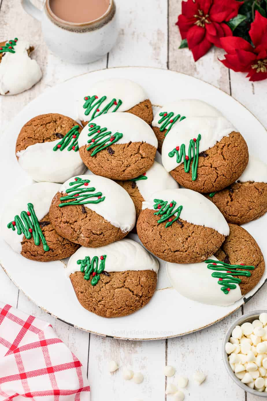 Plate of molasses cookies decorated dipped in white chocolate and decorated with Christmas trees.