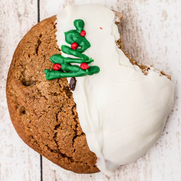 Close up of a molasses cookie dipped in white chocolate and decorated with a chocolate Christmas tree.