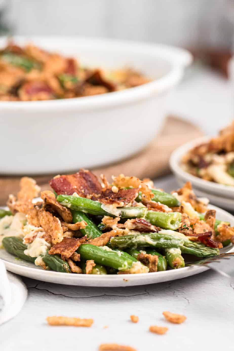 green bean casserole on a plate with bacon pieces, crispy onions and a baking dish in the background