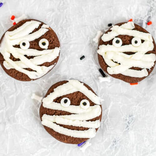 Three chocolate cookies close up decorated with frosting and candy eyes to look like mummies