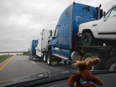 A truck, carrying a truck, carrying a truck, carrying a small truck