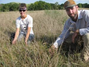Interns Jake and Meg show what a July pasture looks like before grazing.