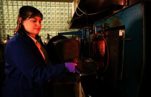 Technician Renee Bigner places poultry litter pellets into a furnace to make biochar via slow pyrolysis. Photo by Stephen Ausmus.