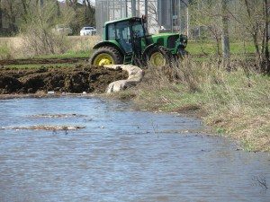 Flooding sinks a farmers tractor in mud.