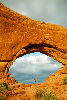 Woman staying with raised hands inside an Arch