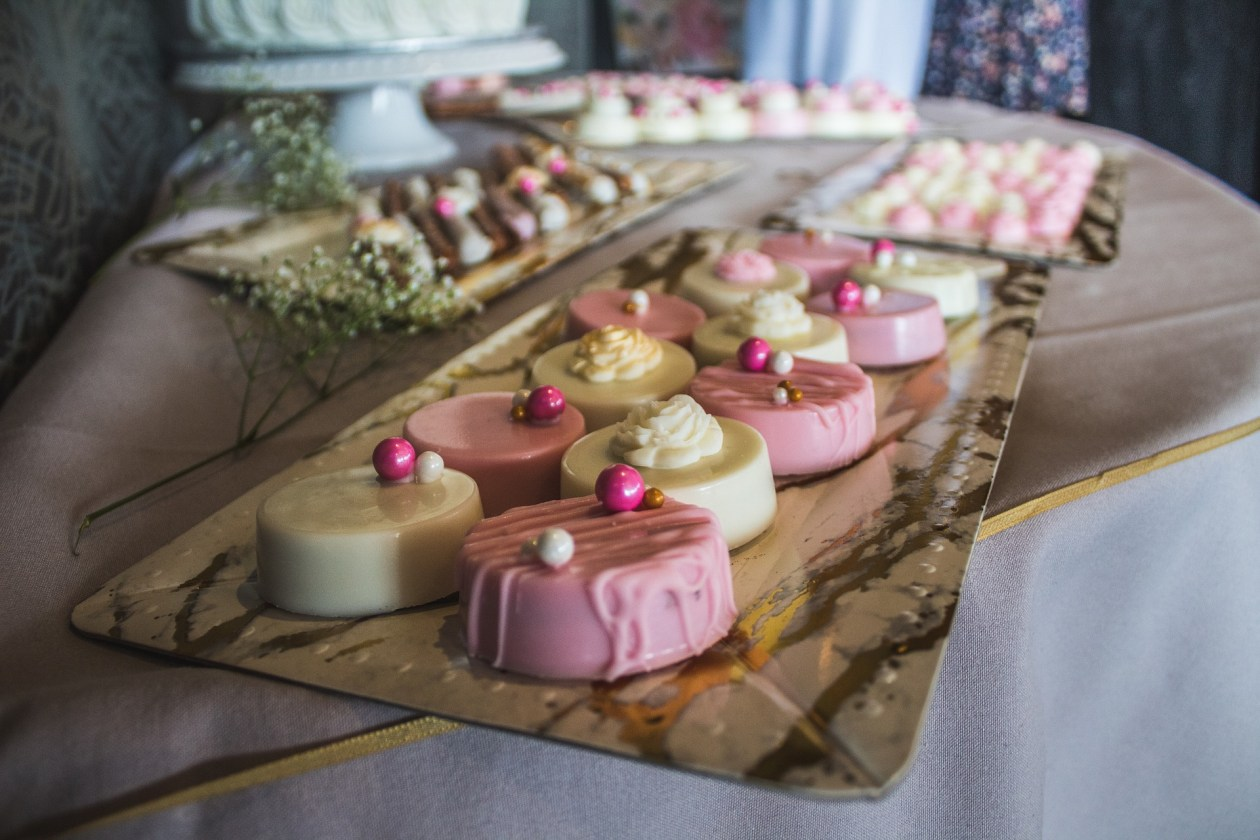 Trays of pretty pink and white cakes. Photo.