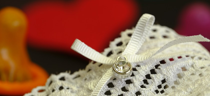 A pair of white lacy knickers sit next to a red heart and a condom. Photo.