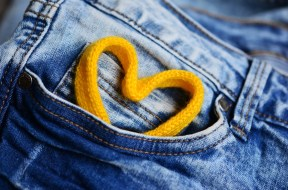 Denim jeans with a yellow shoelace looped into a heart shape sticking out of the pocket. Photo.