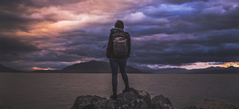A woman wearing a rucksack stands at the top of a hill in front of a sunset. Photo.