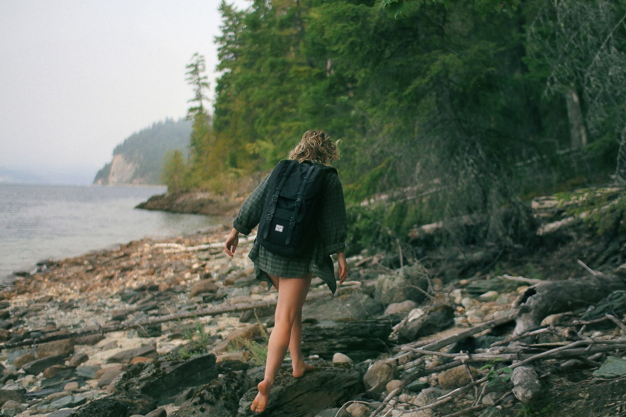 A woman in shorts and hiking boots walks away from the camera across rocky ground. Photo.