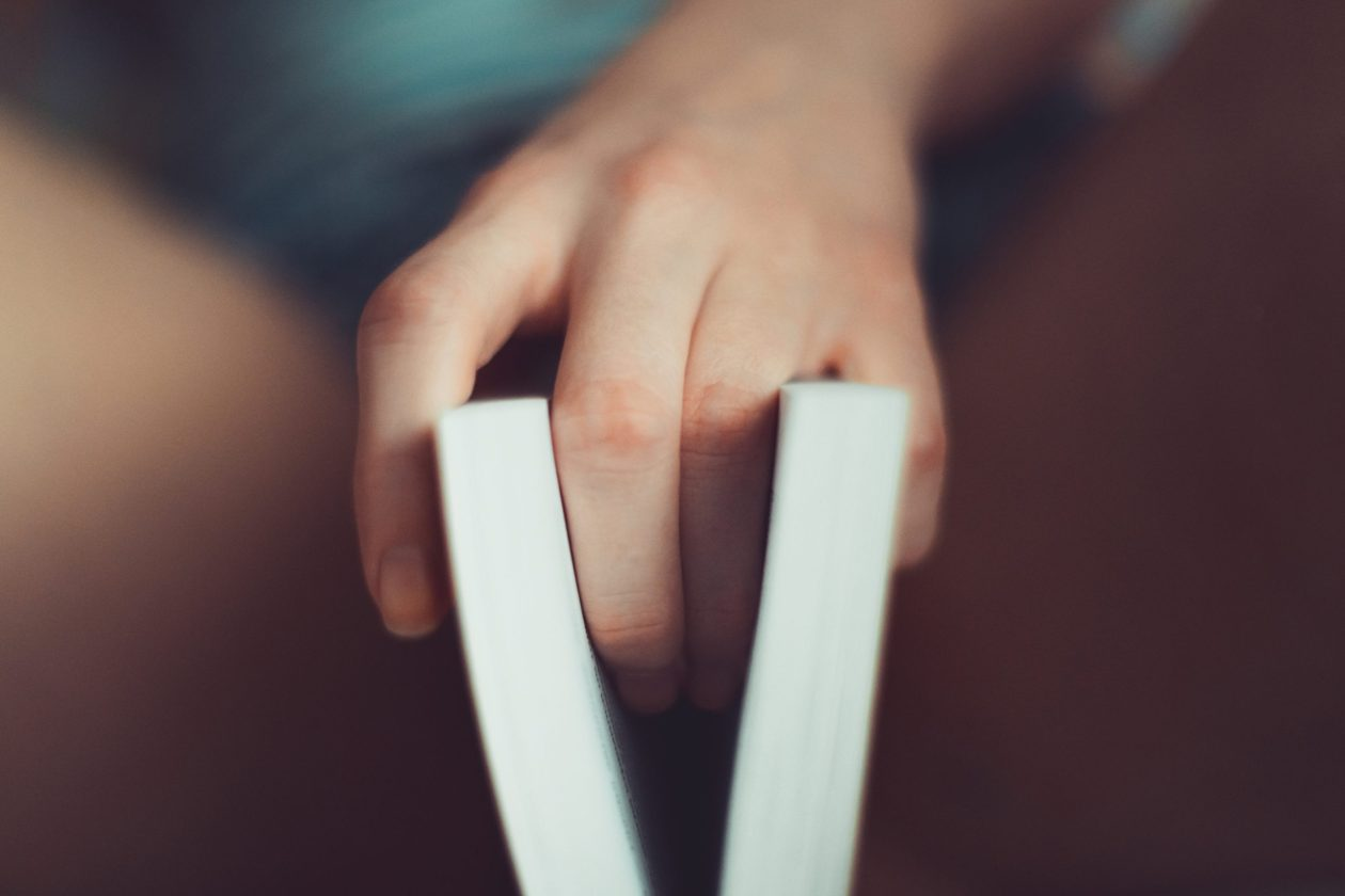 Two fingers on book on bed, symbolising a vagina being touched. Photo.