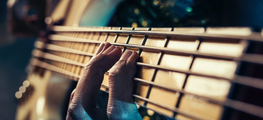 Closeup photo of bass guitar player's fingers. Photo.