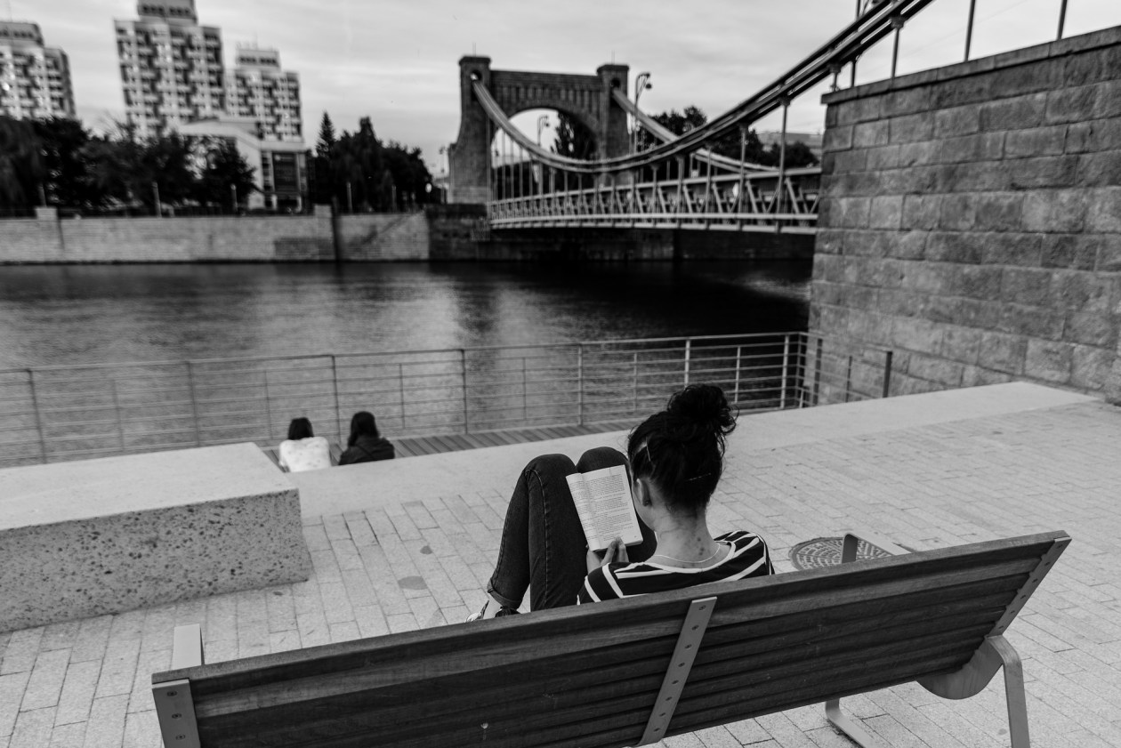 A woman sits on a bench reading by a river. Black and white photo.