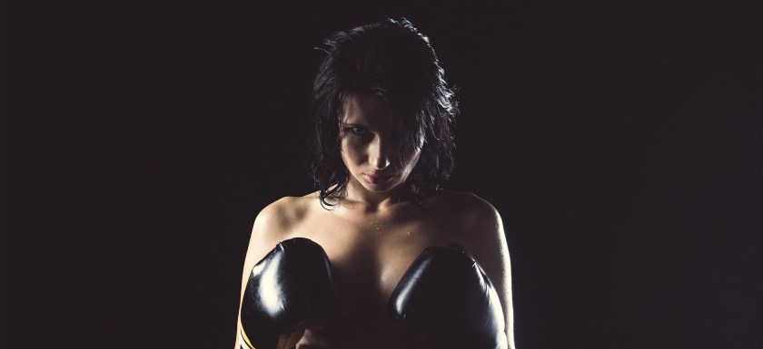 A woman stands naked apart from black boxing gloves held up to her tits. Photo.