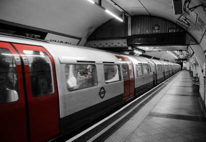 A black-and-white image (with red highlights) photo of a tube train carriage full of people in a London underground station.