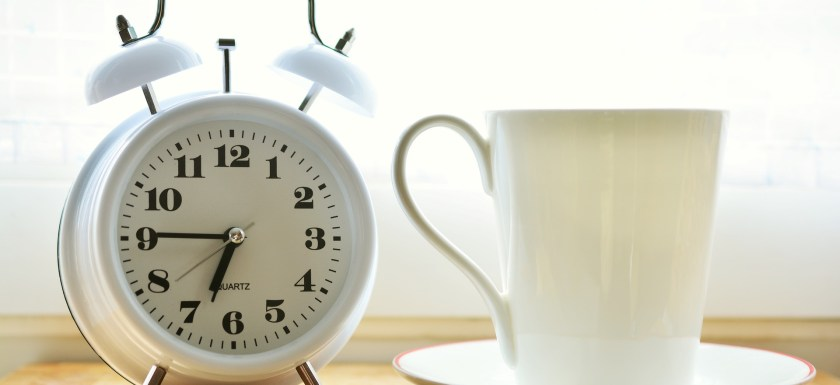 Photo of an analogue, old-fashioned alarm clock and a tea cup and saucer.