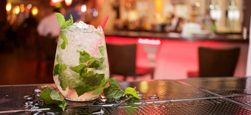 A stock photo of a bar, with blurred lights and bottles in the background and a cocktail with ice and mint leaves in it on the bar.