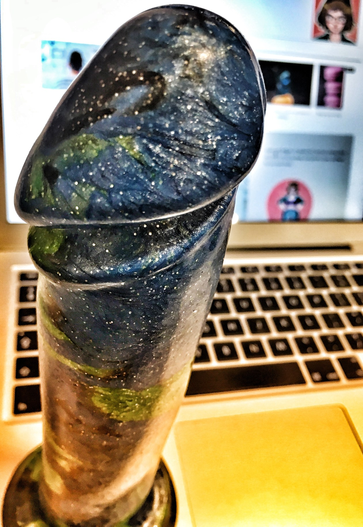 Blue-green glittery dildo suction-cupped to a laptop. Photo.