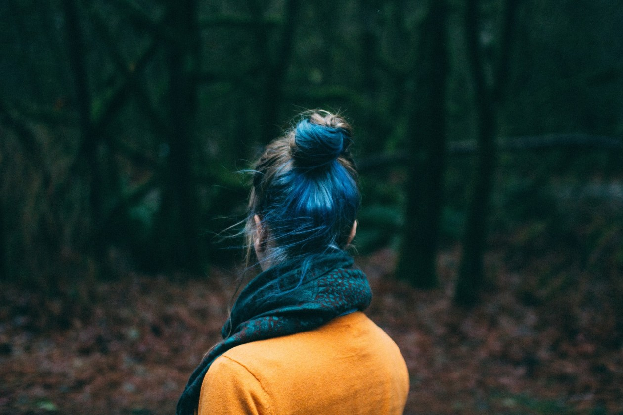 A girl with dyed blue hair and her back to the camera is staring into the woods. Photo.