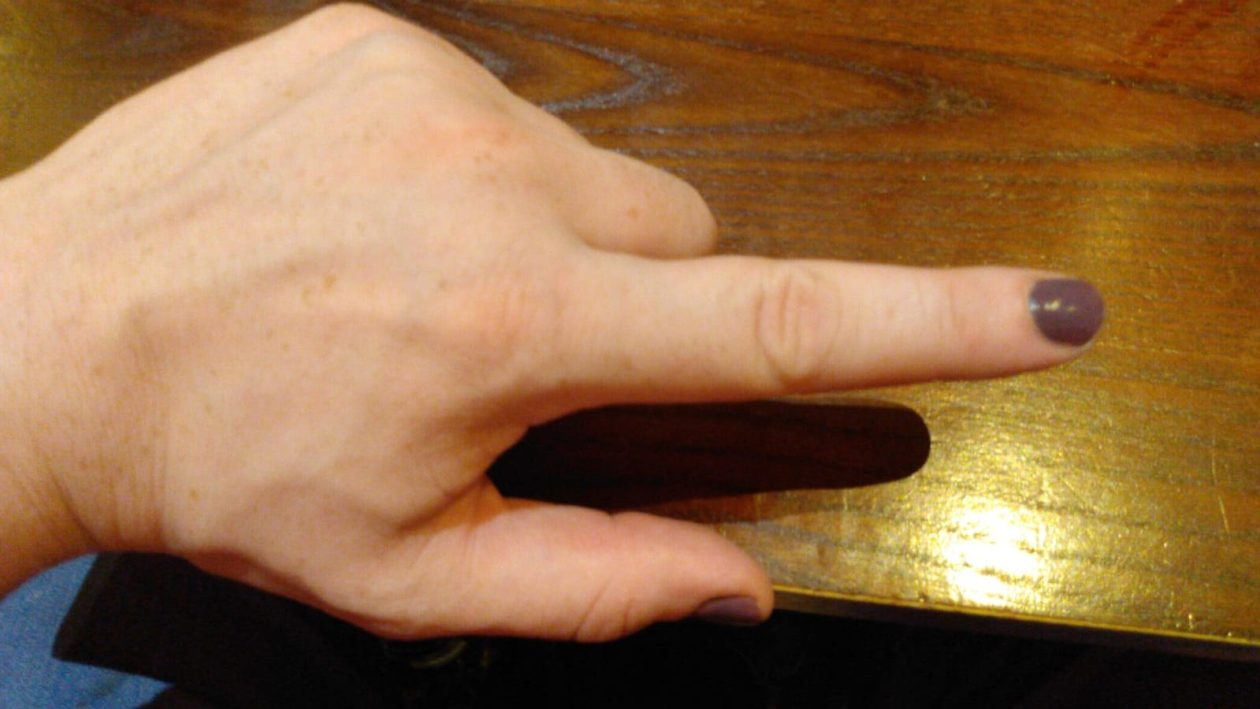 An enby's hand is held over a wooden table, with a single finger extended.