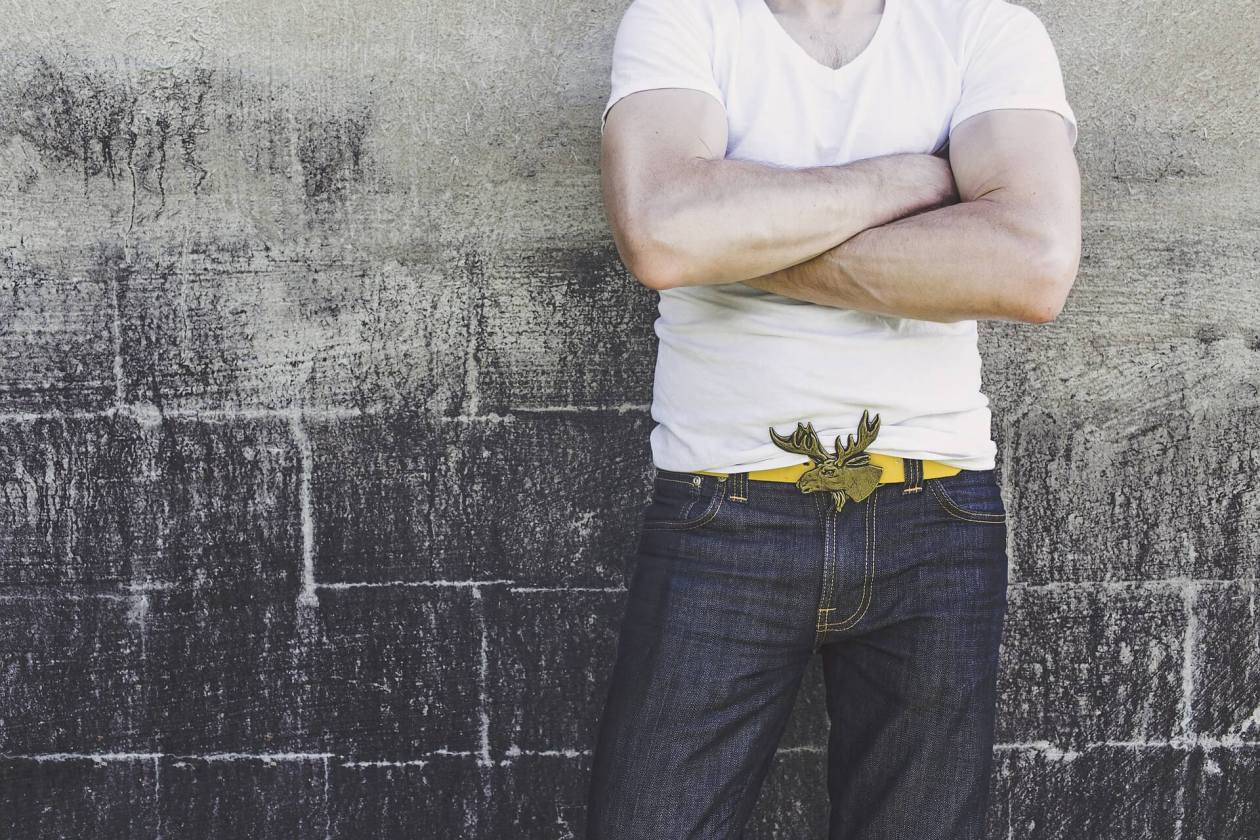 A man in jeans leans against a brick wall with his muscular arms folded. Photo.