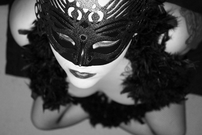 A woman wearing a mask and black lingerie kneels, looking up at the camera. Photo.