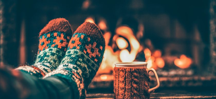 Woman relaxes by warm fire with a cup of hot drink and warming up her feet in woollen socks. Photo.