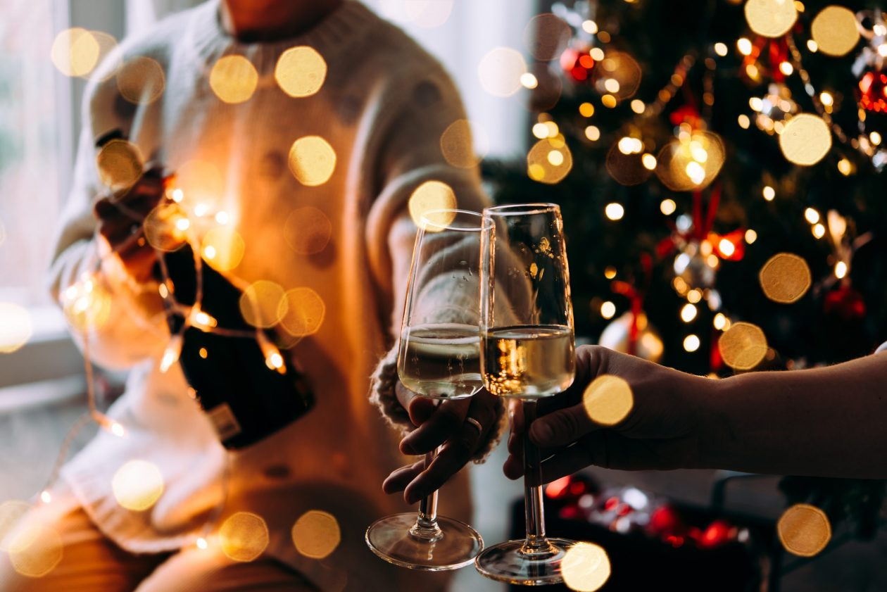 Two people sit in front of a Christmas tree, holding glasses of champagne. Photo.