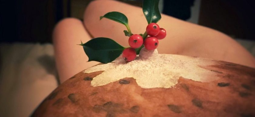 A woman's breast is decorated as a Christmas pudding. Photo.