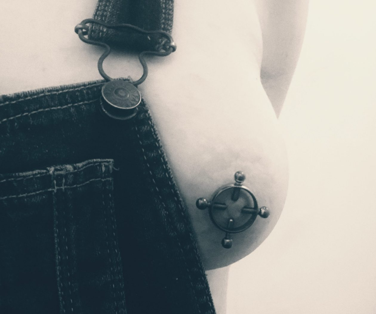 Dungarees are pulled aside to expose a nipple with a temporary piercing on it. Photo.