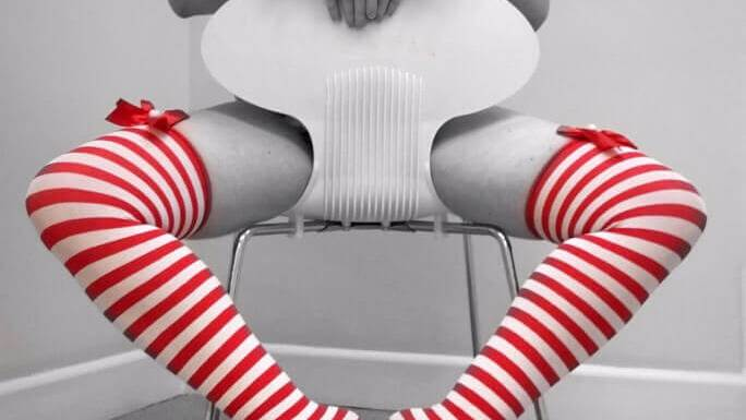 A woman sits backwards on a chair, so her crotch is obscured and her striped stockings and tits are on display. Photo.