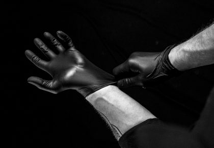 A pair of hands pulling on black latex gloves. Photo.