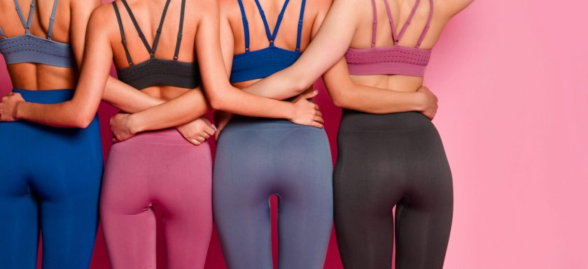 Four women with their arms around each other are wearing bright running leggings and sports bras. Photo.