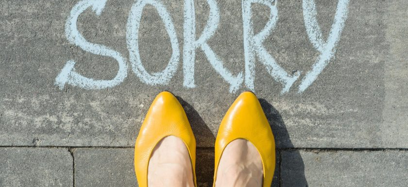 Femme feet wearing yellow heels next to 'sorry' written on asphalt in chalk. Photo.